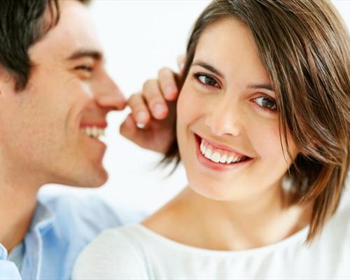 Мужчина говорит женщине на ухо