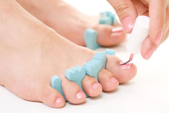женские ноги в процессе обрезного педикюра