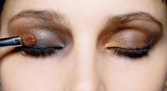 девушка наносит тени на глаза