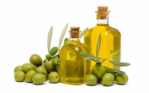 бутылки с маслом и зеленые оливки лежат на столе