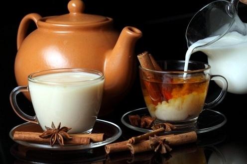 чашки с чаем и молоком стоят на столе