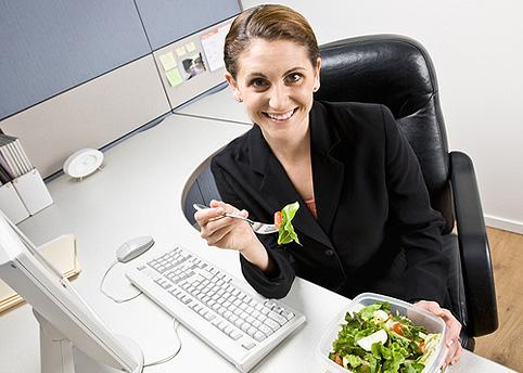 девушка ест салат в офисе