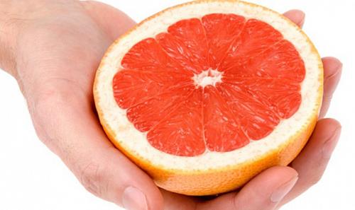 половинка грейпфрута в руке