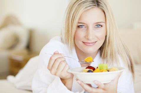 девушка держит тарелку с фруктами