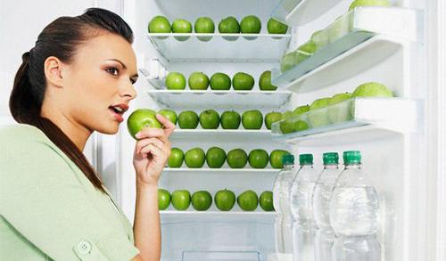 девушка у холодильника с яблоками