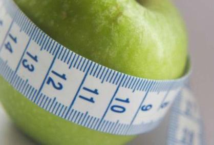 измерительная лента и зеленое яблоко