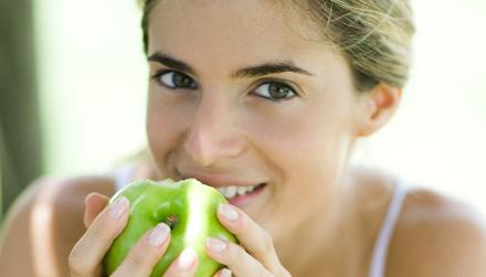 девушка ест зеленое яблоко