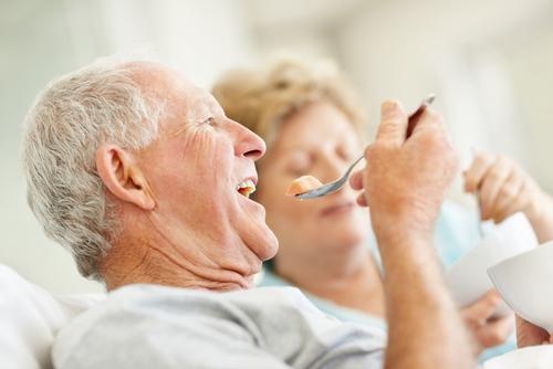 пожилой мужчина ест ложкой
