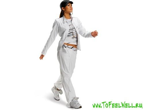 девушка в белом спортивном костюме идет