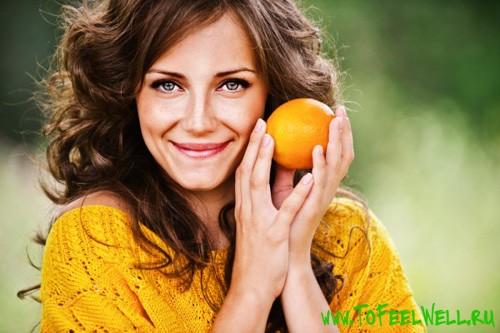улыбающаяся девушка с апельсином