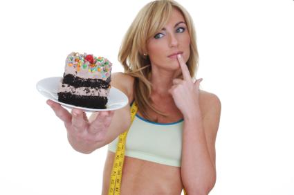 спортивная девушка смотрит на торт