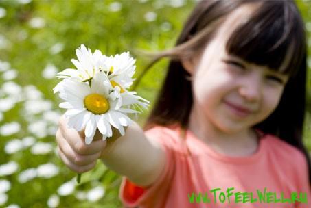 девочка держит в руках ромашки
