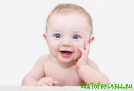 младенец с голубыми глазами улыбается
