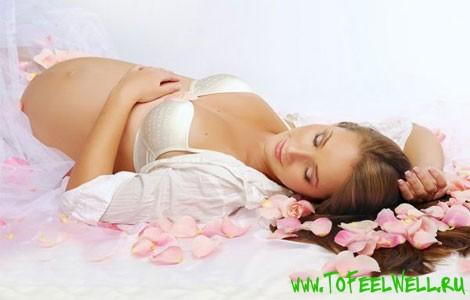 беременная девушка лежит на белом
