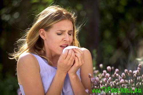 девушка на фоне цветов чихает