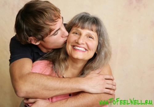 парень обнимает седую женщину