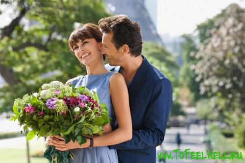 обнимает девушку с букетом цветов