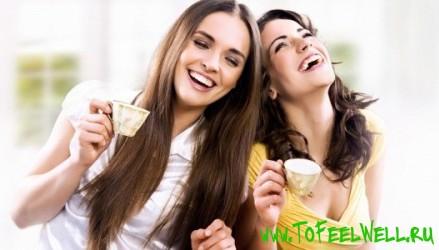 девушки держат чашки в руках и смеются