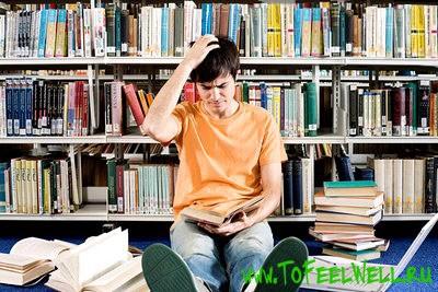 парень смотрит в книгу и чешет голову