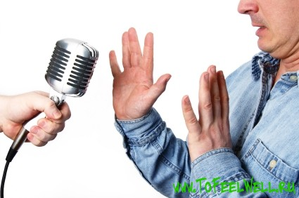 мужчина отталкивает руками микрофон