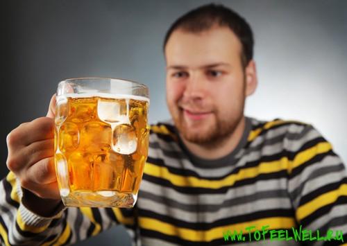 мужчина в полосатой рубашке смотрит на кружку с пивом
