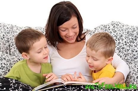 женщина с детьми сидит и смотрит в книгу