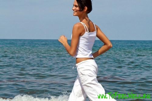 девушка в белом бежит на фоне моря