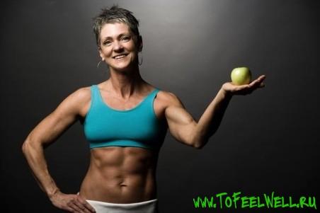 мускулистая женщина держит в руке яблоко