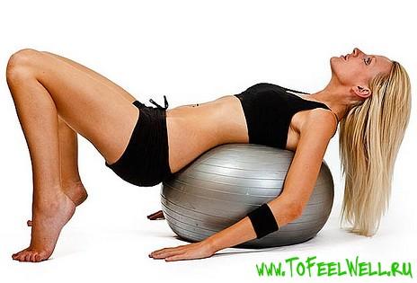 блондинка лежит спиной на мяче