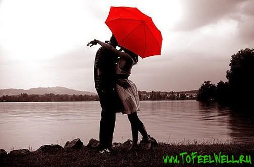 парень с девушкой стоят под красным зонтом