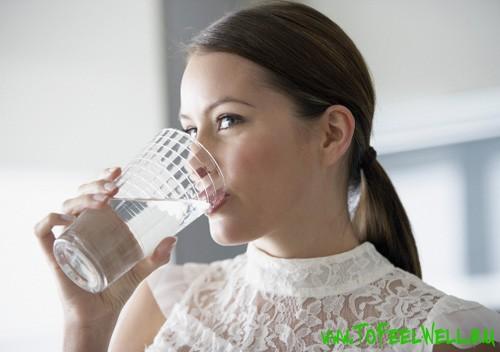 пьет воду из прозрачного стакана