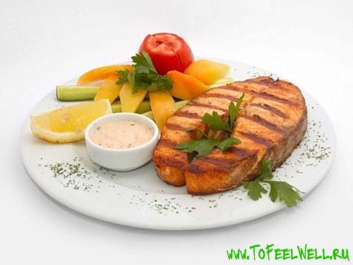 жареная рыба и овощи на тарелке