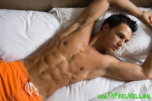мужчина с накачанным прессом лежит в постели