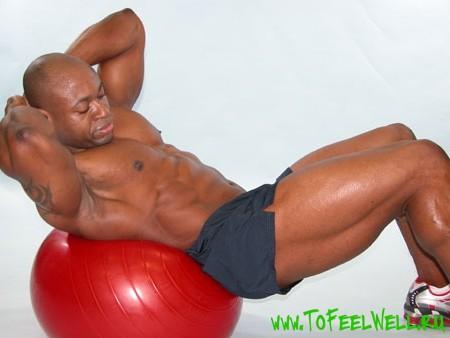 накачанный мужчина лежит на красном шаре