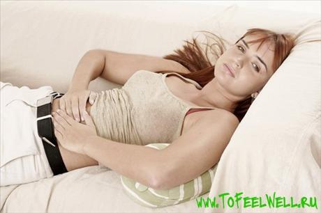 девушка лежит и держится руками за живот
