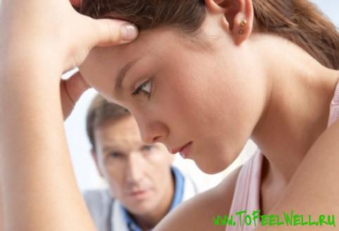 девушка держится руками за голову и смотрит вниз