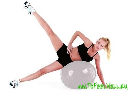 девушка лежит на шаре и тянет ногу вверх