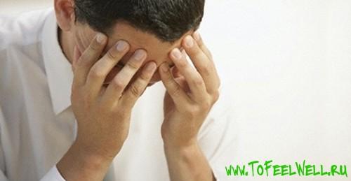 мужчина наклоняет голову и закрывает лицо руками
