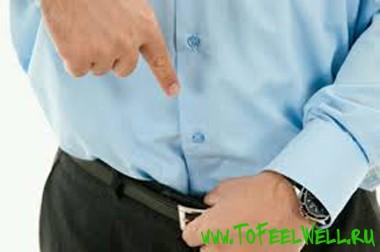 мужчина держится рукой за ремень
