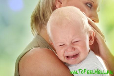 ребенок плачет на руках у женщины