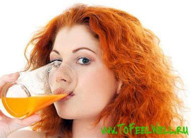 рыжая девушка пьет из стакана