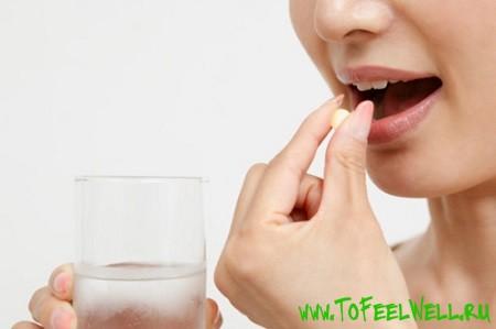 девушка кладет таблетку в рот