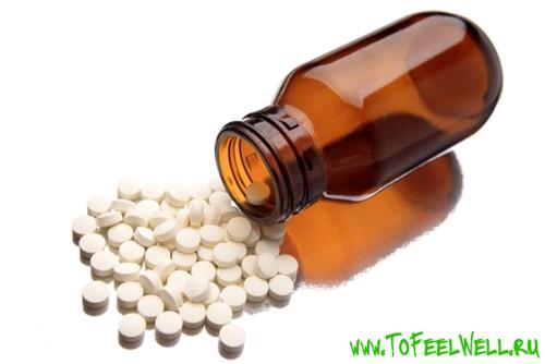 пузырек и таблетки на белом фоне
