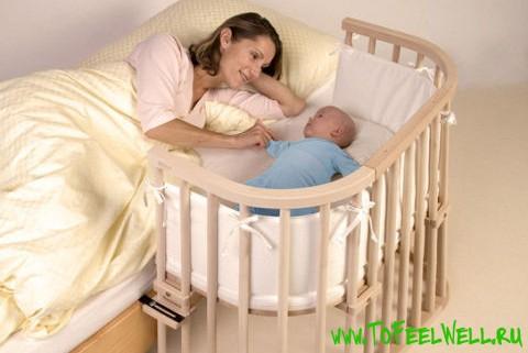 женщина смотрит на ребенка в кроватке