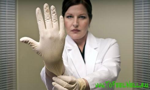 врач надевает резиновые перчатки