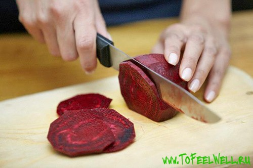 режет свеклу ножом на доске