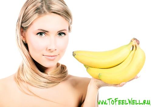 девушка держит бананы в руке на белом фоне