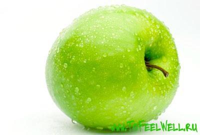 зеленое яблоко в каплях на белом фоне