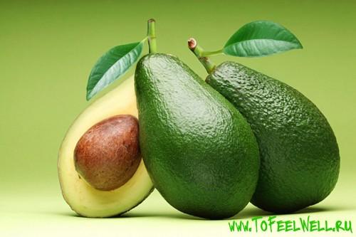 авокадо с косточкой на зеленом фоне