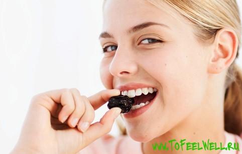 девушка ест чернослив на белом фоне